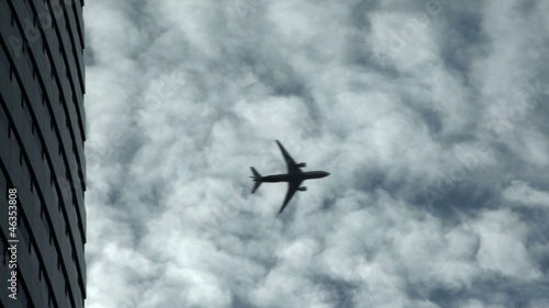 Airplane flying past building with clouds in the background