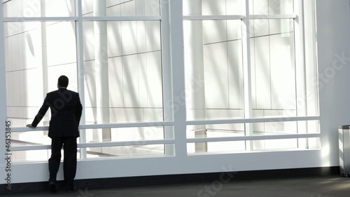 Black businessman walks to window, looks out and leaves