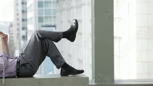 Caucasian businessman laying on a bench text messaging on cell phone