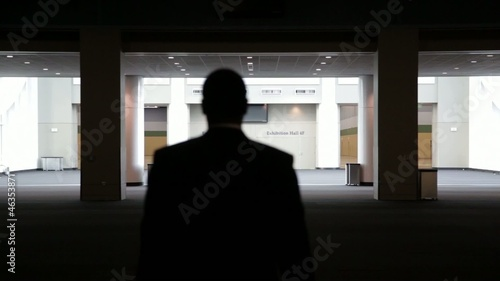 Black businessman walking through empty convention center