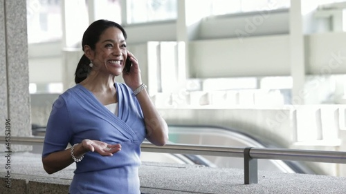 Black businesswoman answers cell phone and laughs