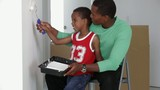African American father with son painting wall