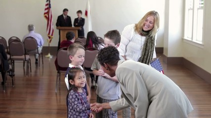 Political candidate shaking hands with children and mother