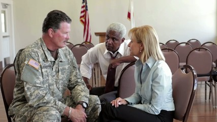 Soldier talking to business people in community center