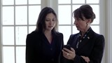 Two businesswoman looking at cell phone and talking