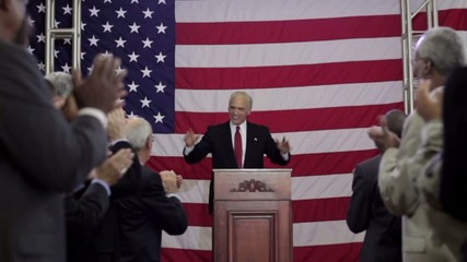 Political candidate with hands up addressing applauding crowd