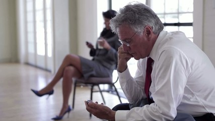 Business people sitting and text messaging on cell phones