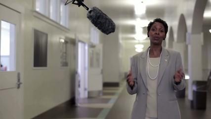 Cameraman interviewing businesswoman in hallway of community center