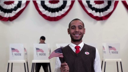 """Hispanic man in front of voting booths waving flag wearing """"i voted"""" sticker"""