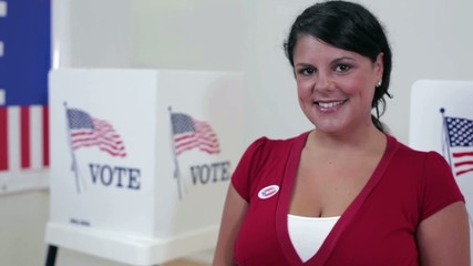 "Hispanic voter standing in front of voting booths wearing ""i voted"" sticker"