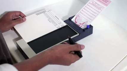 Hispanic man completing ballot in voting booth and leaving with ballot