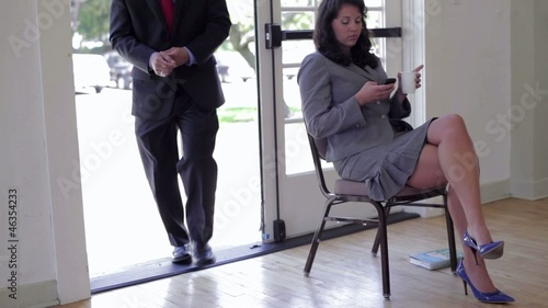 Businesswoman text messaging on cell phone as man walks by