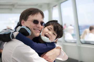 Father hugging disabled son on ferry boat