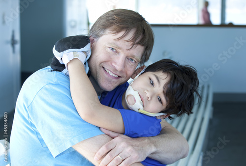 Disabled boy giving father a big hug
