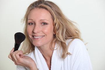 Woman in bathrobe holding make-up brush