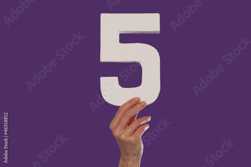 Female hand holding up the number 5 from the bottom