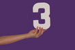 Female hand holding up the number 3 from the left