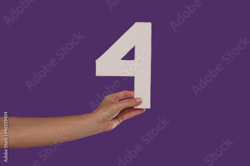Female hand holding up the number 4 from the left