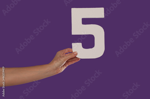 Female hand holding up the number 5 from the left