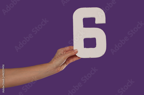 Female hand holding up the number 6from the left