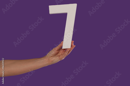 Female hand holding up the number 7 from the left