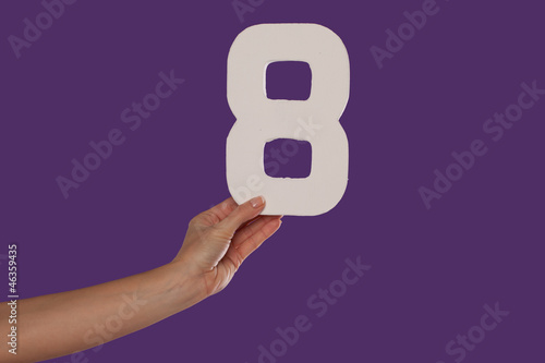 Female hand holding up the number 8 from the left