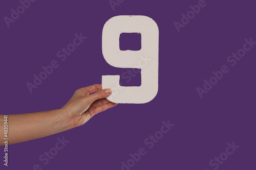 Female hand holding up the number 9 from the left