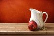 Christmas background with white jug and christmas ornament