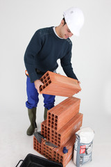 Builder carrying brick