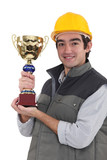 Builder holding trophy