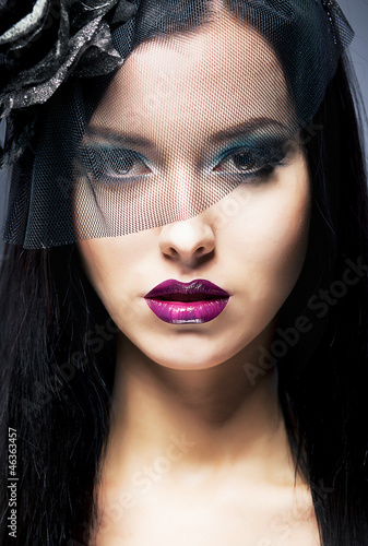 Close-up portrait of a young sad woman with black mourning veil