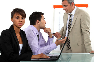 Three businesspeople in a team meeting