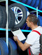 Car mechanic looking for a tire with registration certificate