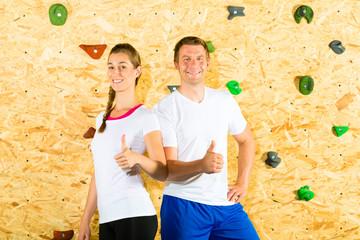 Frau und Mann stehen in Kletterhalle