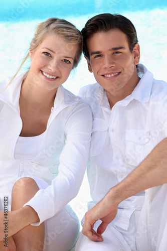Young couple wearing white with a blue sky background