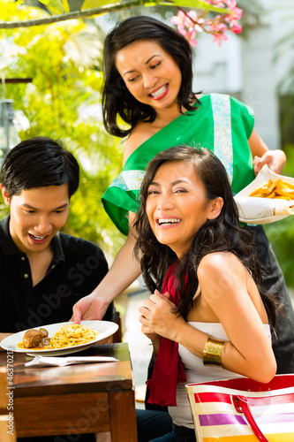 Asian man and woman in tropical restaurant