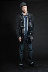 Handsome man dark winter fashion. Studio shot. Wearing cap.