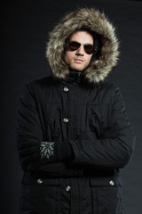 Handsome man dark winter fashion. Studio shot. Wearing glasses.