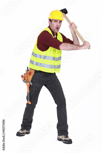 Construction worker smashing with a sledgehammer