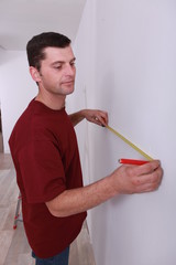 Man measuring wall