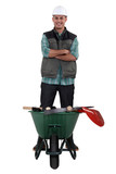 Man stood with wheelbarrow full of tools