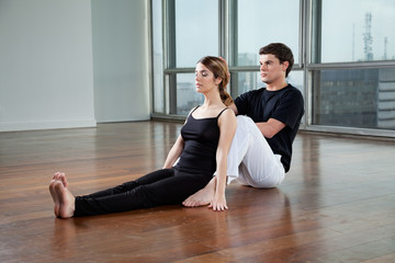 Yoga Instructor Helping Woman With A Pose