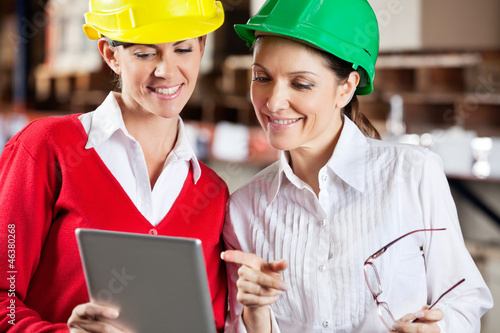 Female Supervisors Using Digital Tablet At Warehouse