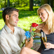Young couple with gifts, rosa and champagne, outdoor