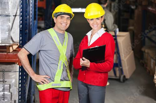 Supervisor Holding Clipboard Standing With Foreman At Warehouse