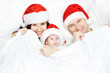 Christmas family with baby smiling in red hat in white bed