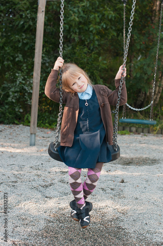 girl in british school uniform sitting on a swing