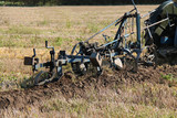 A Vintage Plough Cutting a Furrow in a Field. poster