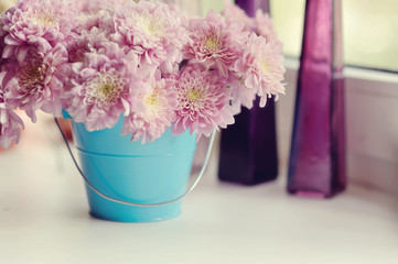 beautiful delicate bouquet of pink chrysanthemums in a blue buck