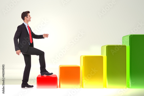 smiling business man stepping on a growing graph